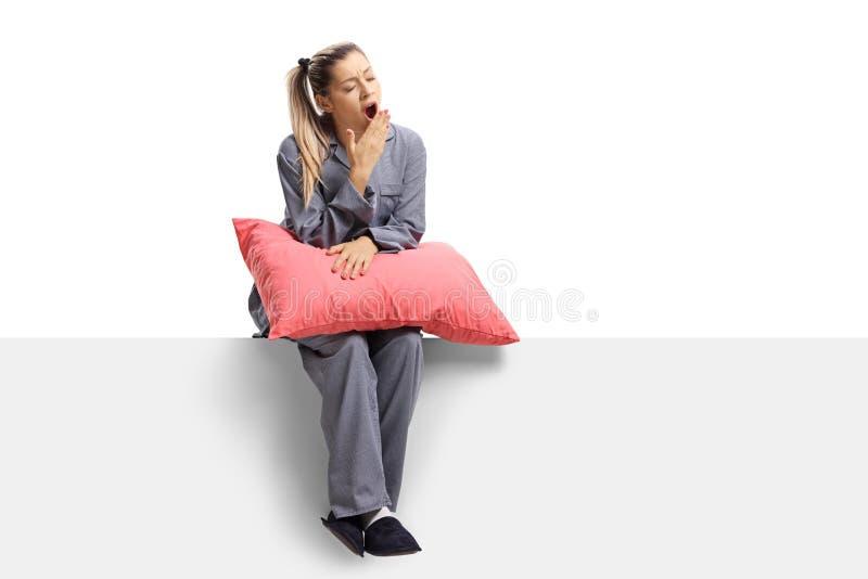Jeune femme somnolente s'asseyant sur un panneau avec un oreiller et baîllant photo stock