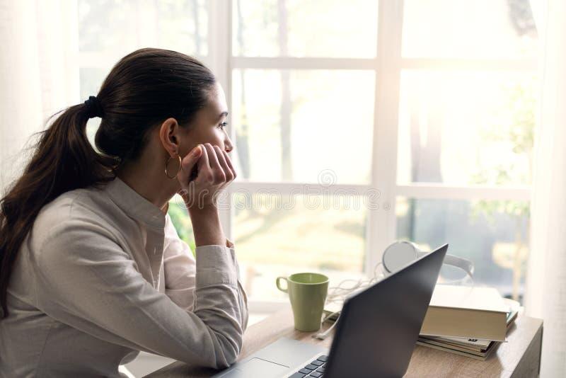 Jeune femme songeuse à la maison regardant loin images libres de droits