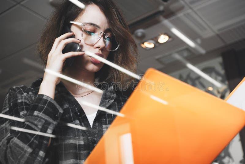 Jeune femme songeuse d'affaires en verres parlant quelque chose sur le pho images libres de droits