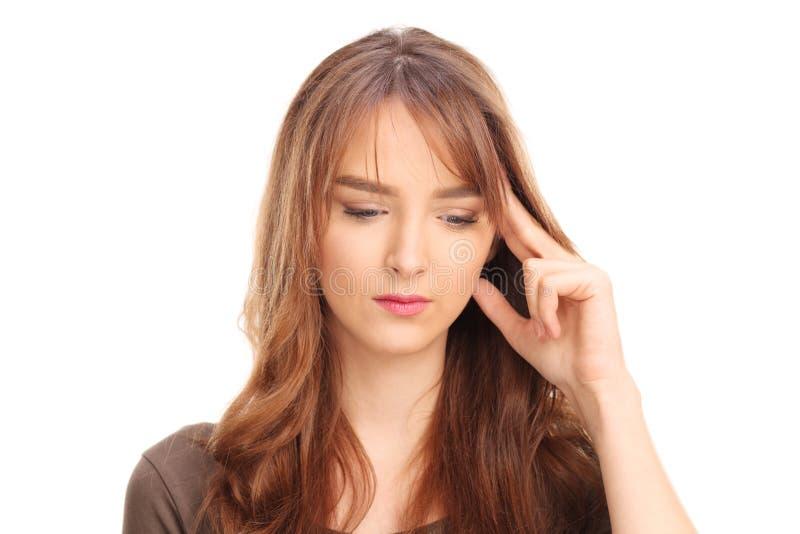 Jeune femme songeuse essayant de se rappeler quelque chose photo stock