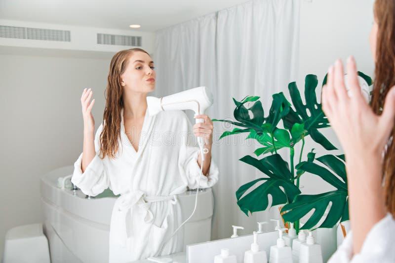 Jeune femme songeuse faisant un brushing à ses cheveux dans la salle de bains photo libre de droits