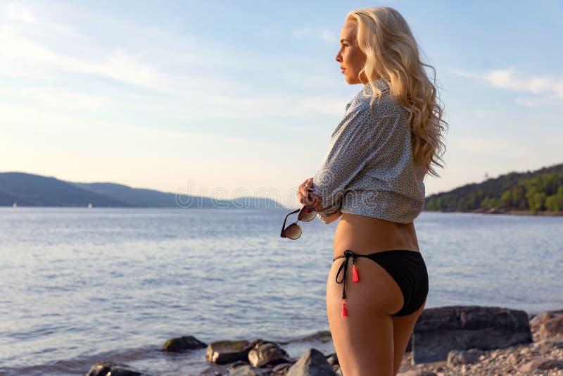 Jeune femme songeuse seul se tenant à la plage en été images stock