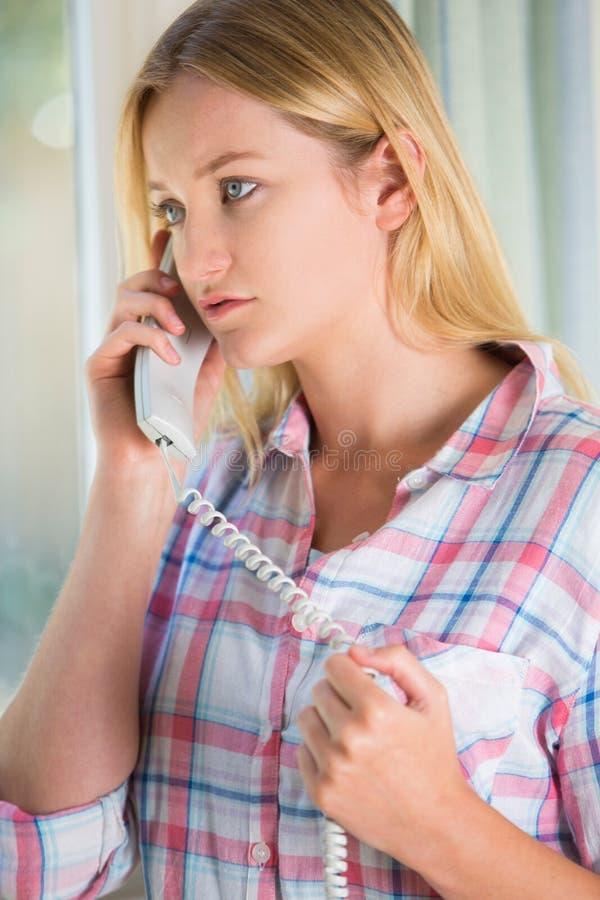 Jeune femme soucieuse téléphonant le service d'assistance photo stock