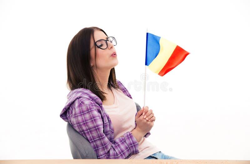 Jeune femme soufflant sur le drapeau français photographie stock libre de droits