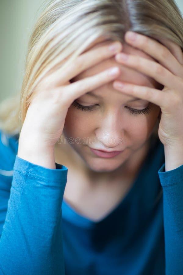 Jeune femme souffrant de la dépression avec la tête dans des mains photos stock