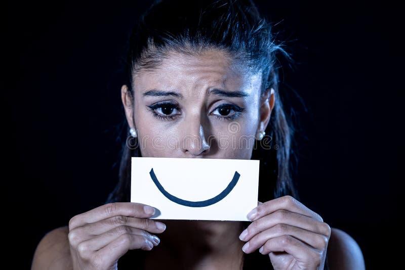 Jeune femme souffrant de la dépression cachant sa tristesse et peine derrière un sourire tiré images libres de droits