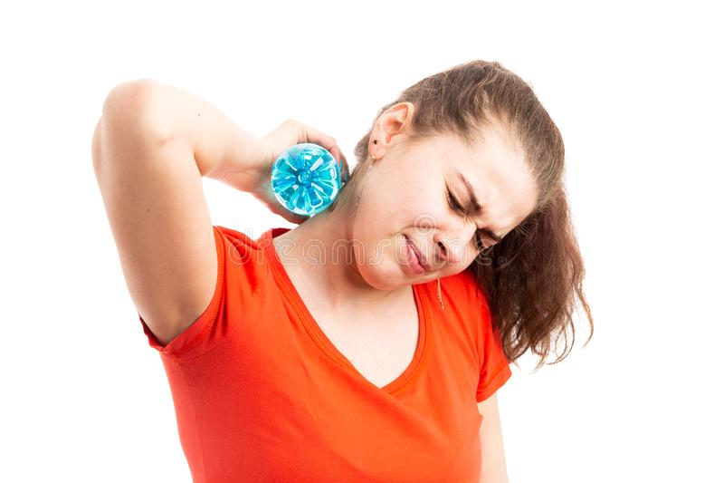 Jeune femme souffrant du temps chaud se refroidissant avec la bouteille d'eau images libres de droits