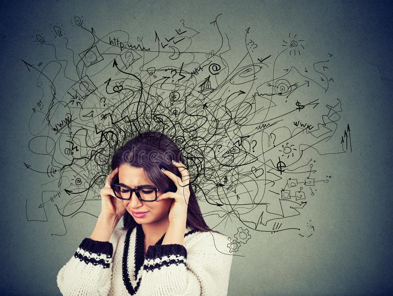 Jeune femme soumise à une contrainte réfléchie en verres avec un désordre dans sa tête photographie stock