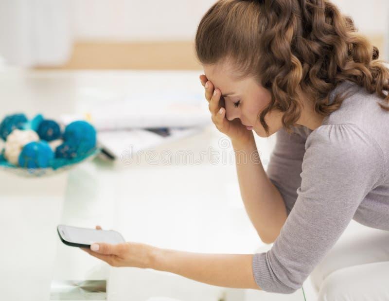 Jeune femme soumise à une contrainte tenant le téléphone portable images stock