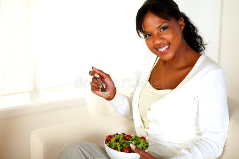Jeune femme souriant à vous tout en mangeant de la salade photos stock