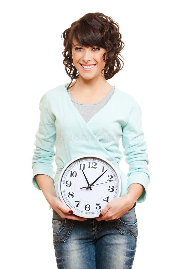 Jeune femme souriant avec l'horloge photos stock