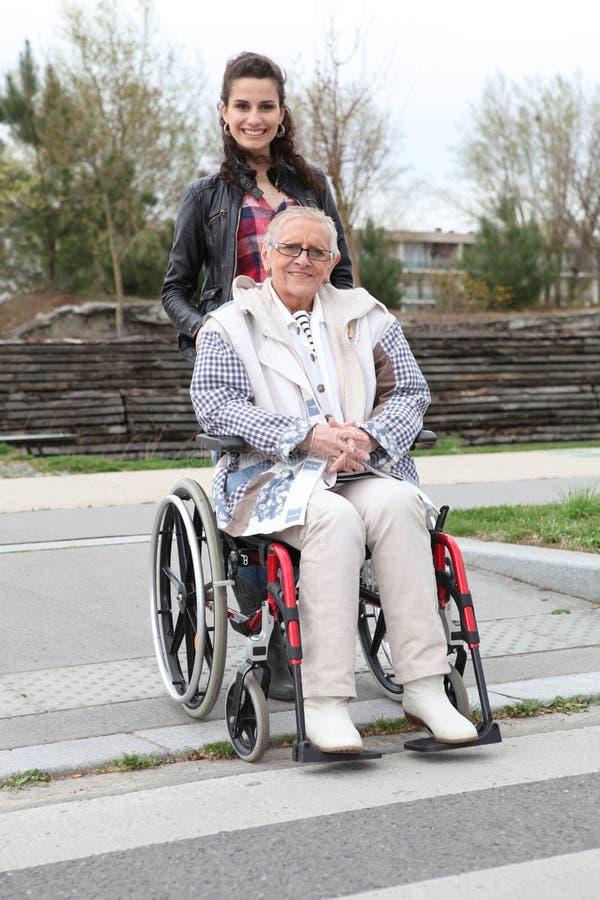 Jeune femme souriant avec le femme aîné dans le wheelchai images libres de droits