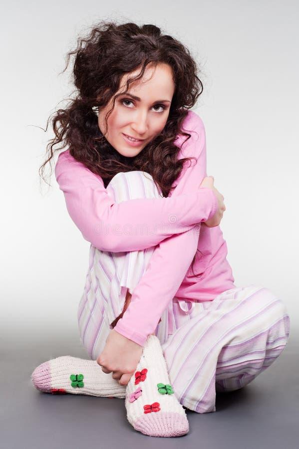 Jeune femme souriant dans des pyjamas roses photos stock
