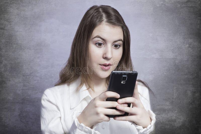 Jeune femme souriant et à l'aide d'un smartphone photographie stock libre de droits