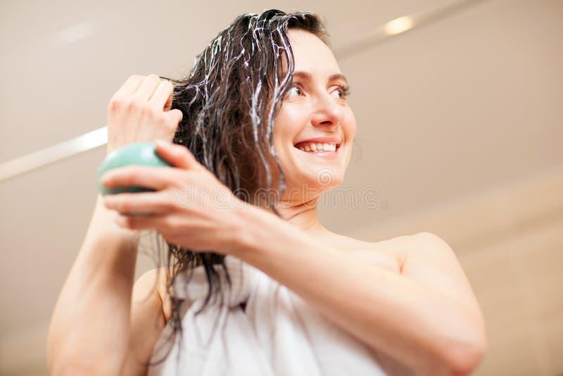 Jeune femme souriante en train d'appliquer un masque à cheveux dans une salle de bains photos stock