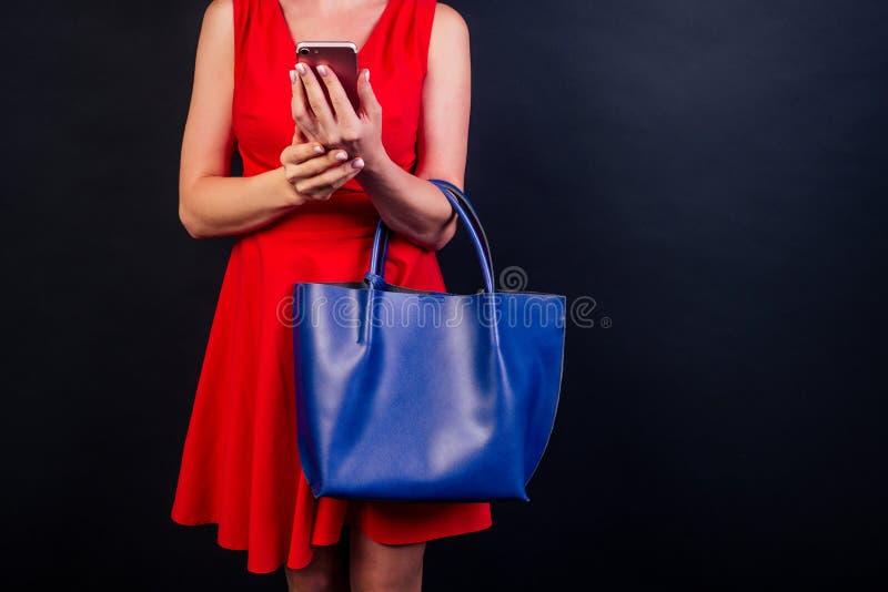 Jeune femme souriante tenant un sac et un téléphone portable en vacances de vendredi noir Fille dans un studio sombre avec copie photo stock