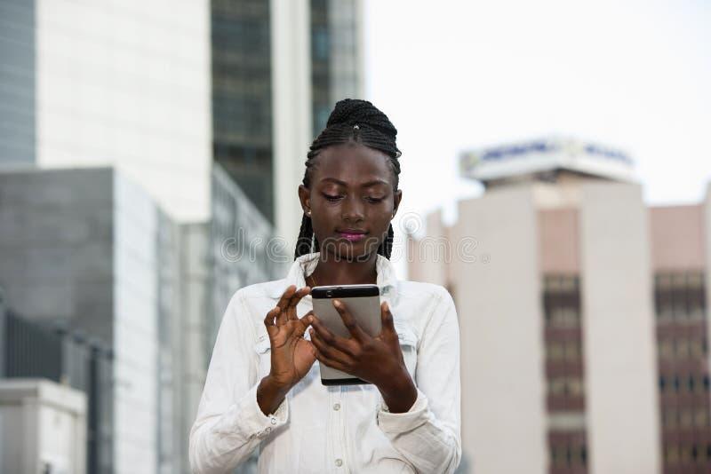 Jeune femme souriante tenant un smartphone photo libre de droits