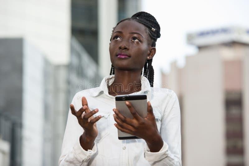 Jeune femme souriante tenant un smartphone photographie stock