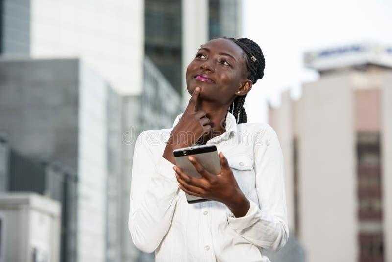 Jeune femme souriante tenant un smartphone photo stock