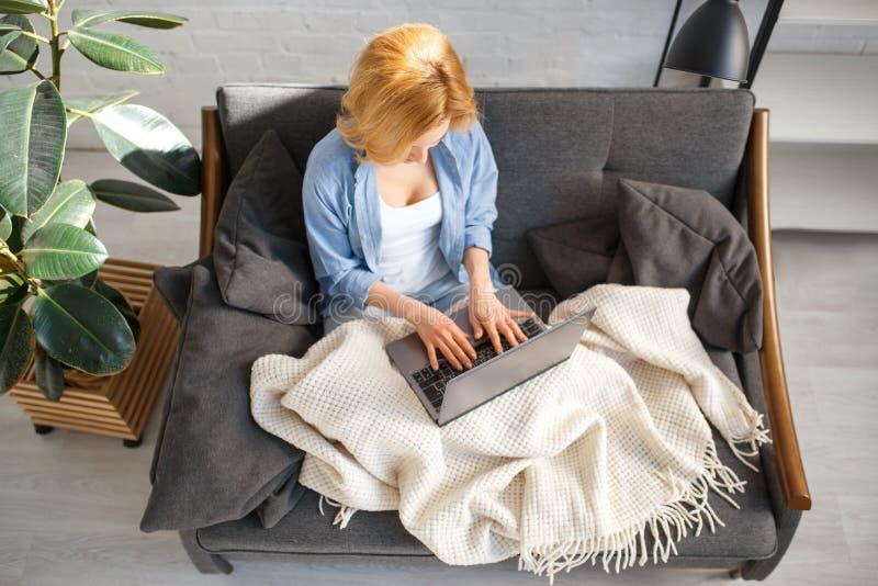 Jeune femme sous une couverture utilisant l'ordinateur portable sur le divan images libres de droits