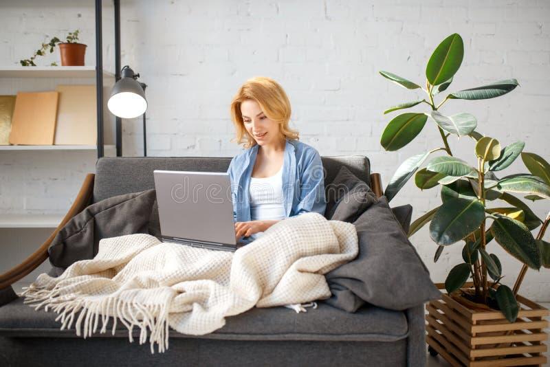 Jeune femme sous une couverture utilisant l'ordinateur portable sur le divan image stock