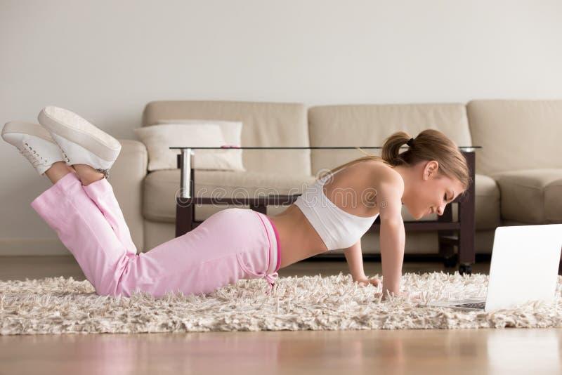 Jeune femme sportive établissant à la maison, faisant des pousées photographie stock
