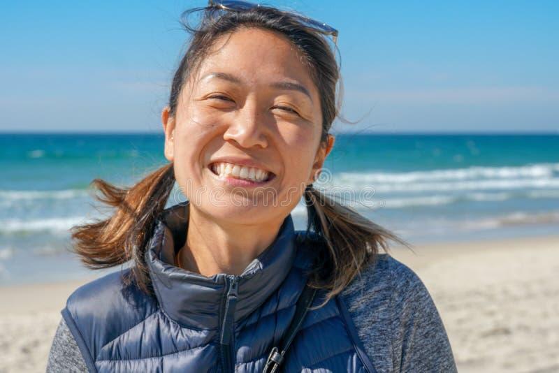 Jeune femme sportive asiatique de sourire à la plage photo libre de droits