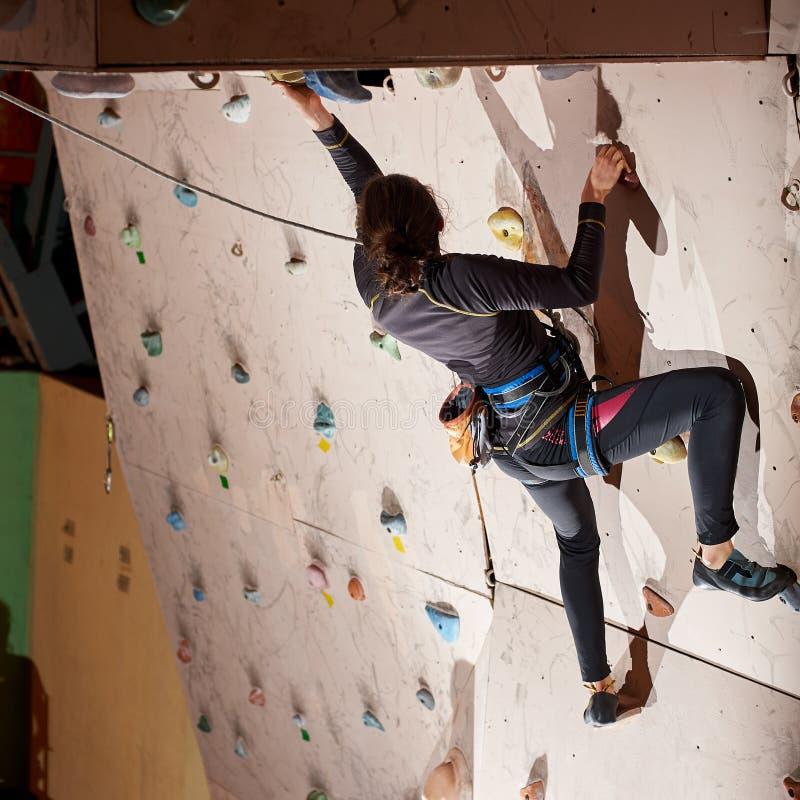 Jeune femme sportive atteignant le dessus du mur bouldering artificiel tout en s'exerçant dans le gymnase bouldering à l'intérieu photos stock