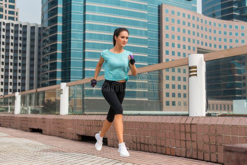 Jeune femme sportive attirante courant sur le trottoir photo libre de droits