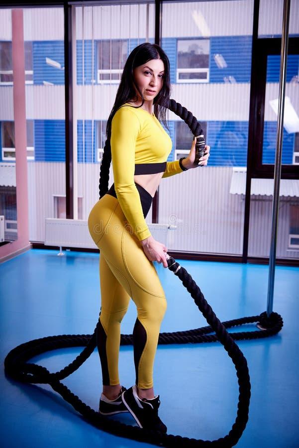 Jeune femme sportive avec des cordes pour la formation convenable croisée dans le gymnase de forme physique image stock