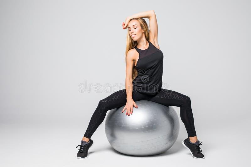 Jeune femme sportive avec la bille gymnastique sur un fond blanc photos libres de droits
