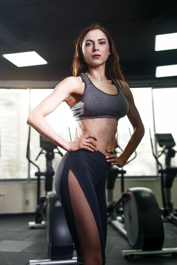 Jeune femme sportive avec le beau corps montrant des muscles après séance d'entraînement dans le gymnase image libre de droits
