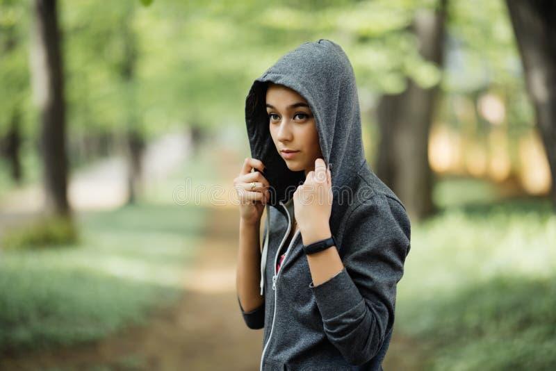 Jeune femme sportive avec le pull molletonné à capuchon écoutant la musique de son téléphone intelligent au parc de ville photos stock