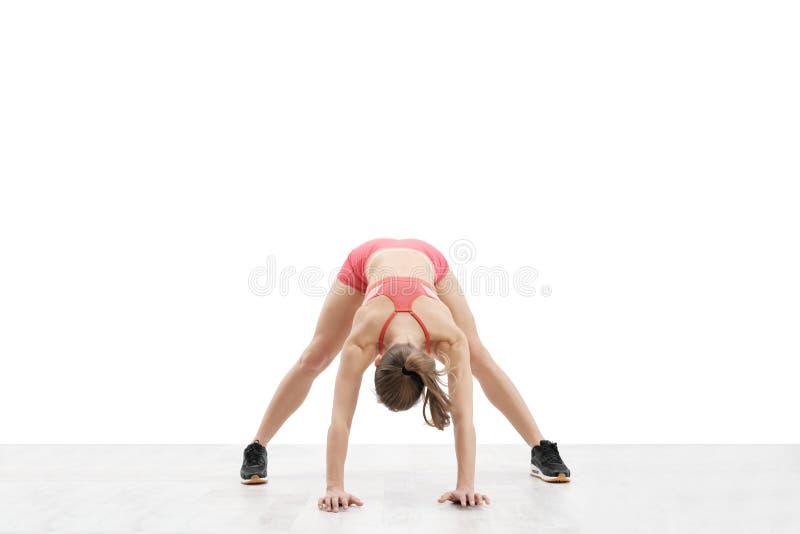 Jeune femme sportive avec un corps sportif, des écouteurs sans fil de port et des vêtements de sport rouges étirés au-dessus d'un image stock