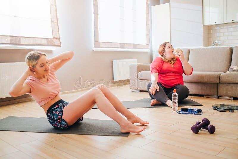 Jeune femme sportive bien batie faisant l'ABS dans le salon Modèle positif de corps de poids excessif mangeant de la nourriture i photographie stock libre de droits
