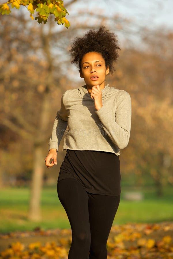 Jeune femme sportive courant dehors en parc image libre de droits