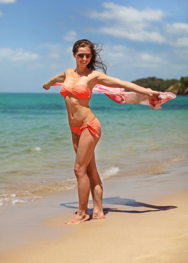 Jeune femme sportive dans des vêtements de bain oranges de bikini et lunettes de soleil, marchant sur la plage, tenant l'écharpe  images libres de droits