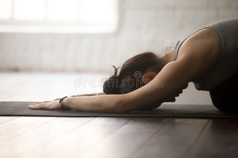 Jeune femme sportive dans la pose de Balasana, studio blanc de grenier, plan rapproché photo libre de droits