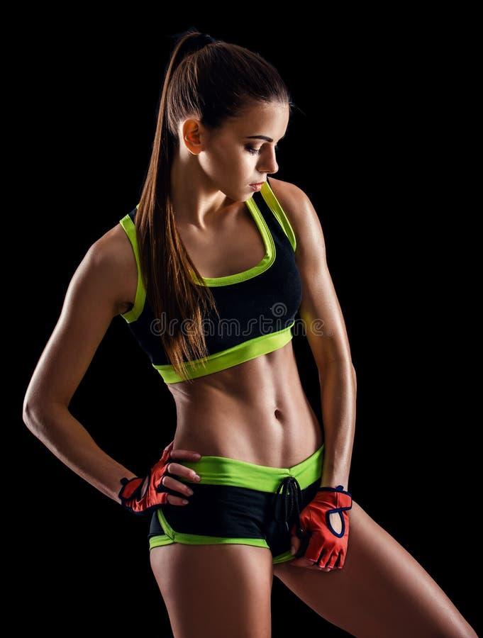 Jeune femme sportive dans les vêtements de sport posant dans le studio sur le fond noir Chiffre femelle idéal de sports image libre de droits