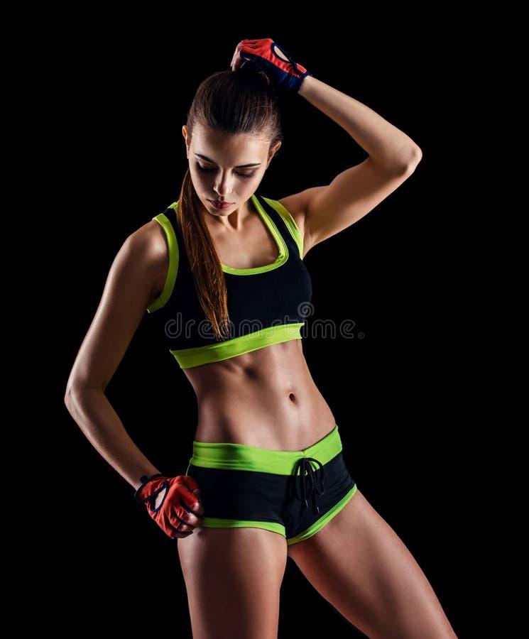 Jeune femme sportive dans les vêtements de sport posant dans le studio sur le fond noir Chiffre femelle idéal de sports photos stock