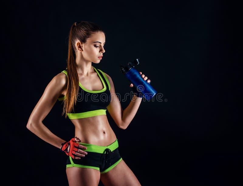 Jeune femme sportive dans les vêtements de sport posant dans le studio sur le fond noir Chiffre femelle idéal de sports image stock