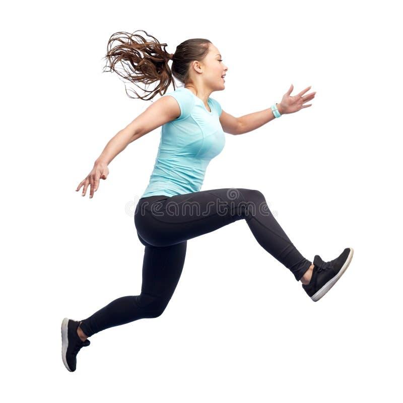 Jeune femme sportive de sourire heureuse sautant en air photographie stock libre de droits
