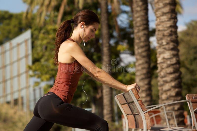 Jeune femme sportive faisant étirant la séance d'entraînement par un banc de parc dehors photo libre de droits
