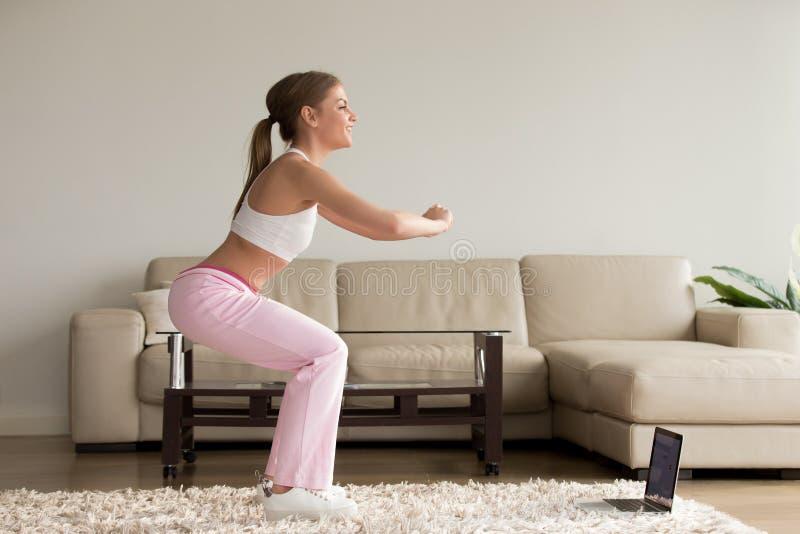 Jeune femme sportive faisant des exercices accroupis à la maison, trainin en ligne photo stock