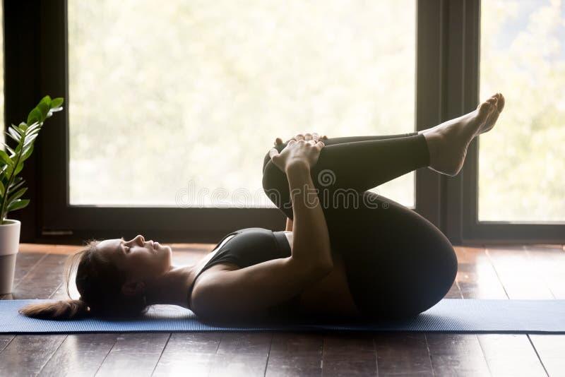 Jeune femme sportive faisant des pilates ou la pose d'Apanasana de yoga photos libres de droits