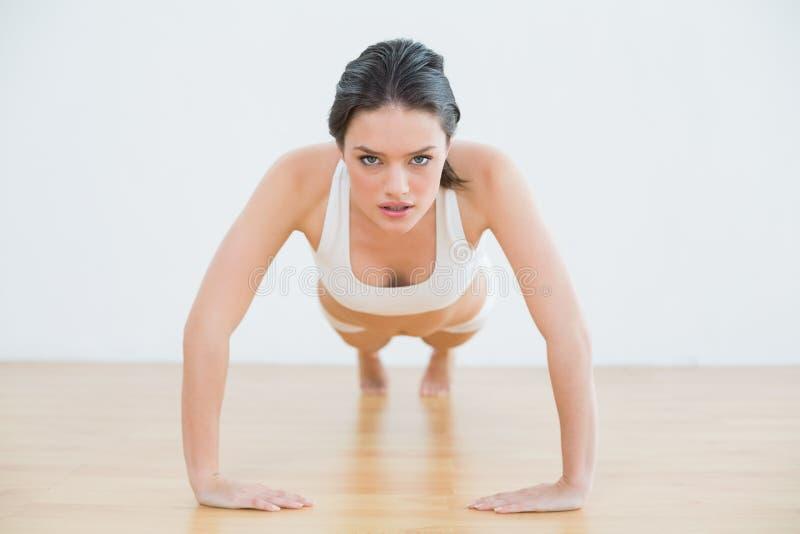 Jeune femme sportive faisant des pousées dans le studio de forme physique photo libre de droits