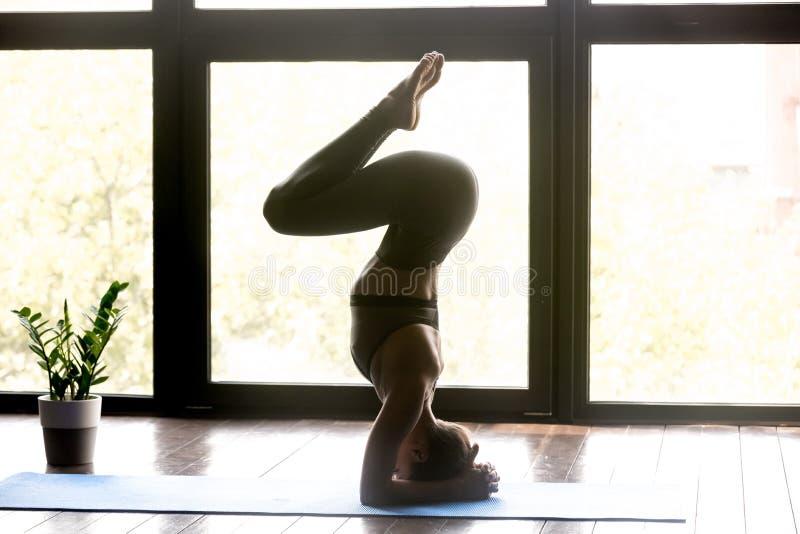 Jeune femme sportive faisant l'exercice de headstand de yoga photo stock