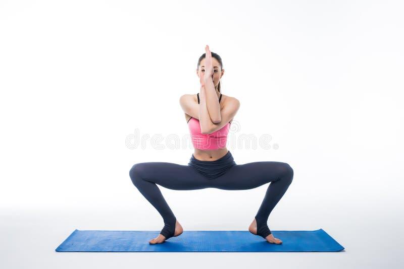 Jeune femme sportive faisant la pratique en matière de yoga d'isolement sur le fond blanc photographie stock