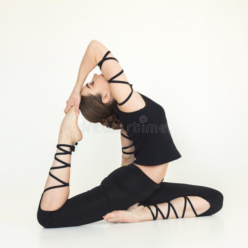 Jeune femme sportive faisant le yoga sur le fond blanc photographie stock