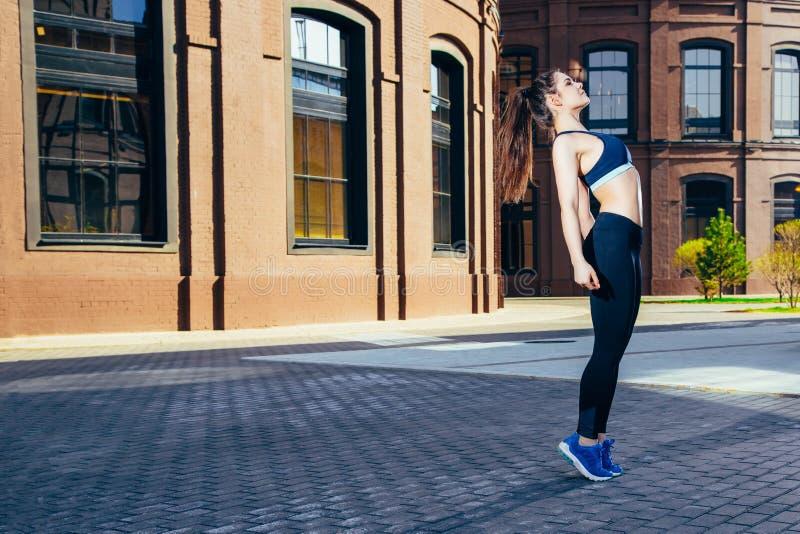 Jeune femme sportive faisant un exercice s'étendant dans la ville photographie stock